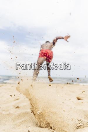 athletischer mann laeuft am strand