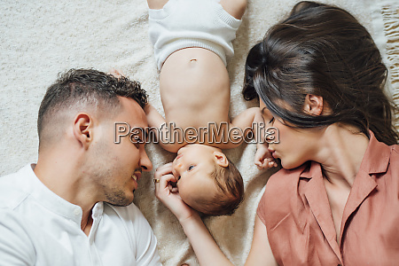 liebevolle eltern liegen mit baby junge