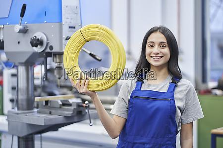 glueckliche arbeiterin haelt aufgerollte kabel in