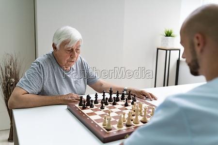 AEltere senior spielen schach mit betreuer
