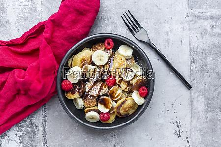 schüssel, mit, hausgemachten, mini-pfannkuchen, mit, bananen, himbeeren, schokoladensauce - 28760902