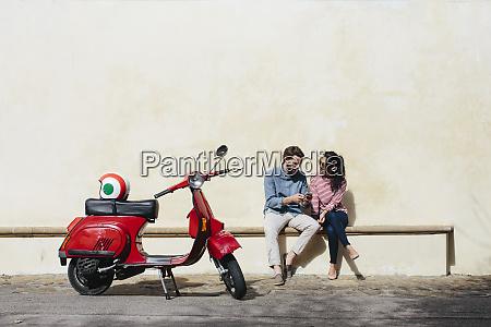 mann mit smartphone waehrend sitzen mit