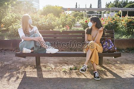 zwei freunde tragen schutzmasken sitzen auf