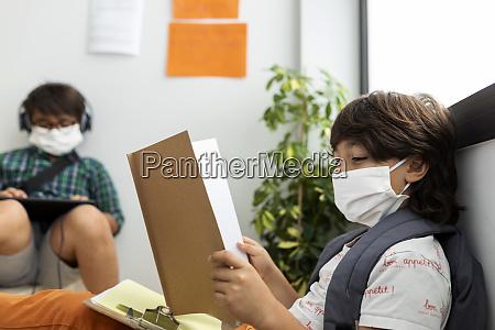 jungen tragen masken studieren waehrend sie