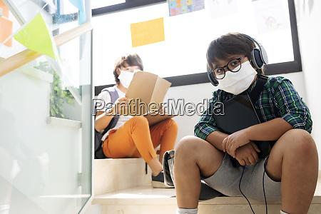 jungen tragen masken sitzen auf stufen