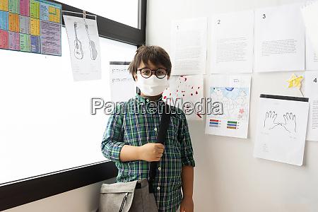 junge traegt maske mit tasche stehen