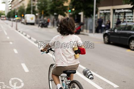 junge haelt skateboard beim fahrradfahren auf