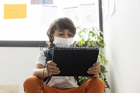 junge traegt gesichtsmaske mit digitalen tablet