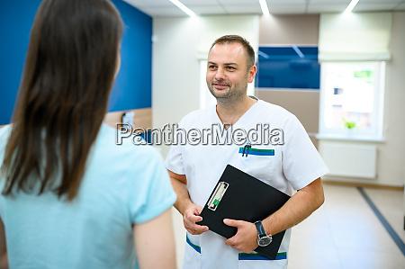 maennlicher arzt spricht mit patient im