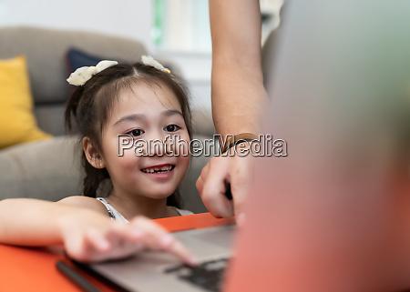 asiatische maedchen grundschueler mit computer laptop