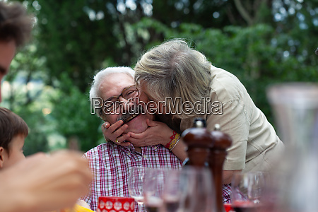 seniorin kuesst mann auf wange