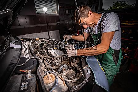 mechaniker mit schraubenschluessel arbeiten und reparaturautomotor