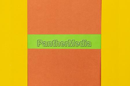 gruener orangefarbener und gelb erbunter papierhintergrund