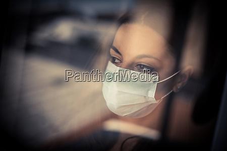 frau traegt eine chirurgische maske durch