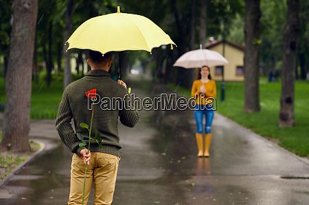 liebespaar mit regenschirmen und rose romantisches