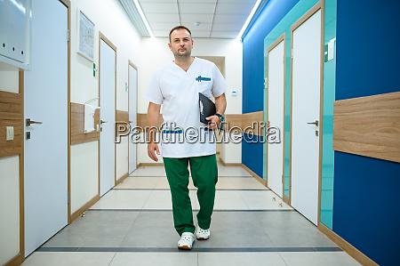 freundlicher maennlicher arzt im klinikflur