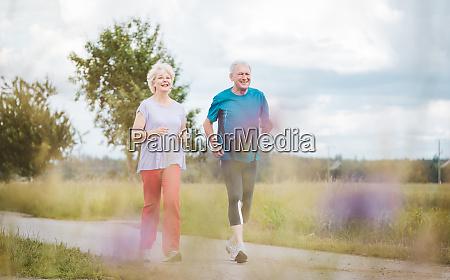 fites und aktives seniorenpaar laeuft im