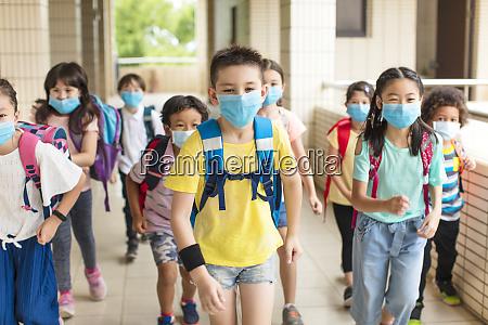 gruppe von kindern tragen gesichtsmaske zurueck