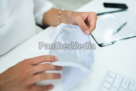 paycheck in open envelope