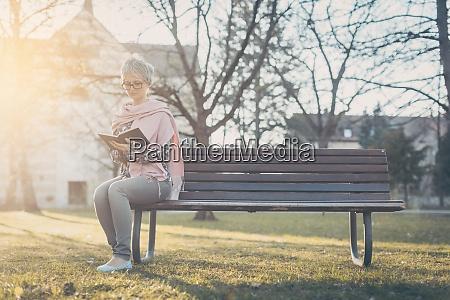 seniorin sitzt allein auf der bank