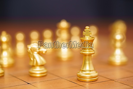 gold koenig schachstueck stehen auf holzschachbrett
