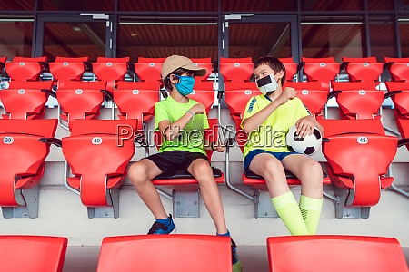 zwei jungen in einem fussballstadion waehrend