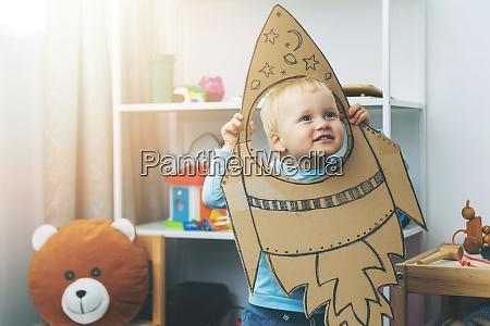 kleiner junge spielt mit pappraumschiff zu