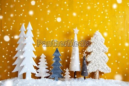 weihnachtsbaeume schneeflocken gelber hintergrund kopierraum