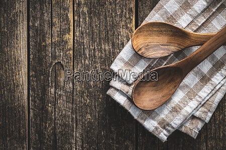zwei holzloeffel auf karierten servietten auf