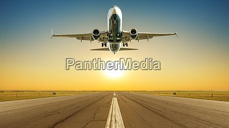 verkehrsflugzeug hebt gegen sonnenuntergang ab