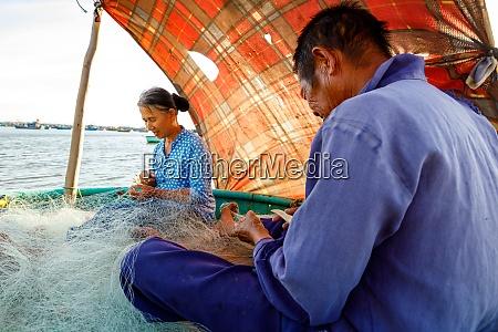 fischer aus vietnam reparieren ein fischernetz