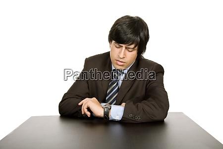 junger besorgter geschaeftsmann auf einem schreibtisch