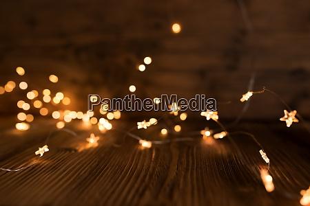 weihnachtsbeleuchtung auf dunklem holz