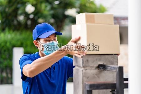 asiatische liefern mann machen kontaktlose paketlieferung