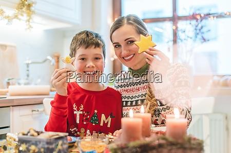 junge und seine mutter mit weihnachtsplaetzchen