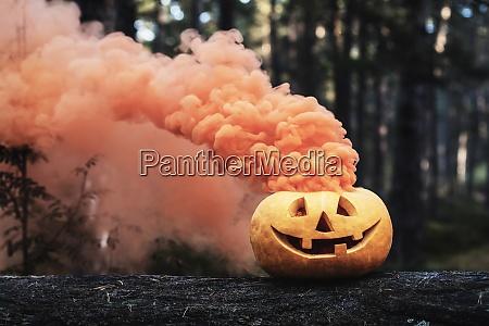 geschnitzte halloween kuerbis mit orange rauch