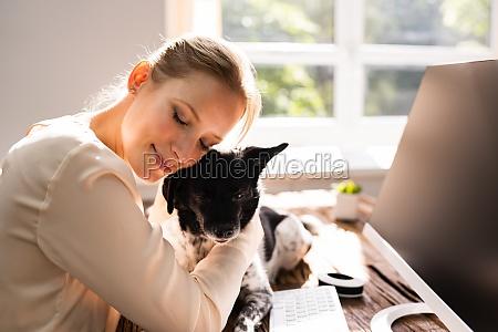 frau umarmt hund im home office