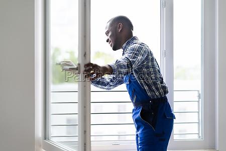 afrikanischer reparaturmann in overalls installationsfenster