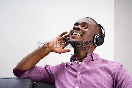 gluecklicher afroamerikanischer mann geniesst musik