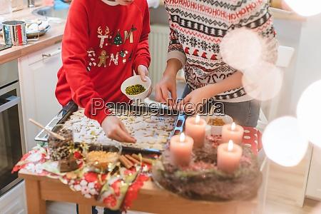 mutter und sohn schmuecken weihnachtsplaetzchen auf