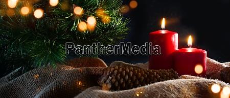 adventskerzen mit weihnachtsschmuck