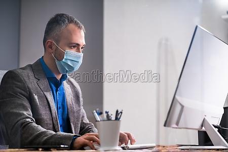 geschaeftsmitarbeiter im buero tragen medizinische masken