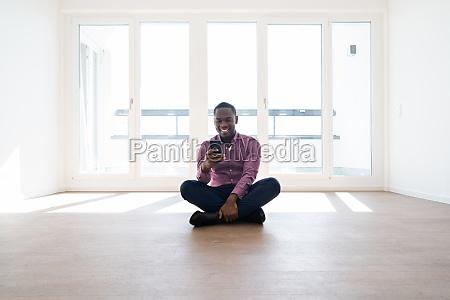 afrikanischer mann sitzt im leeren haus