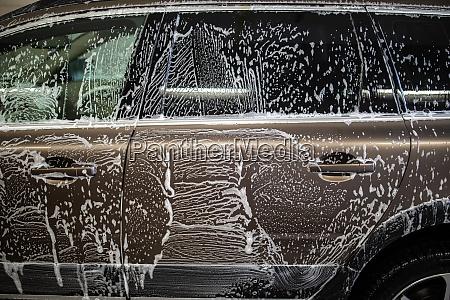 auto in einer waschanlage mit shampoo