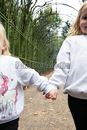 zwei junge maedchen halten haende laufen