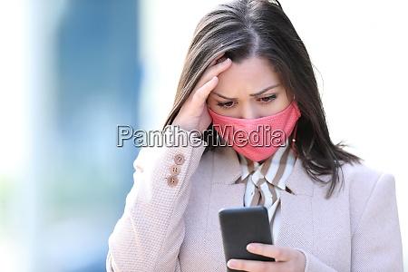 besorgte geschaeftsfrau mit maske lesen telefon