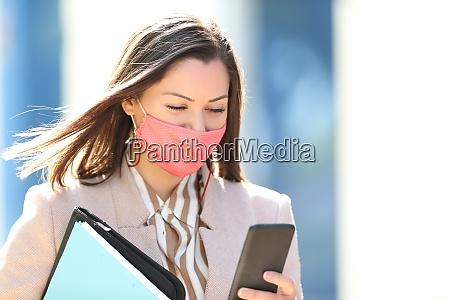 geschaeftsfrau mit maske lesen telefon inhalte