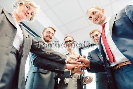 business team stapelt haende die auf