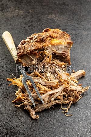 gezogenes schweinefleisch mit gabel auf schwarzem
