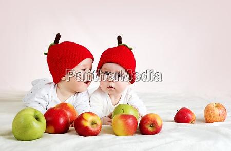 zwei niedliche babys liegen in hueten